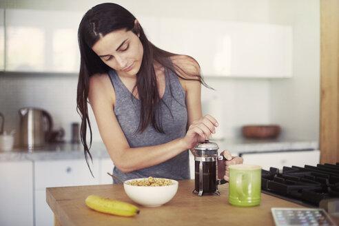 Woman holding coffee jug on table - CAVF22330