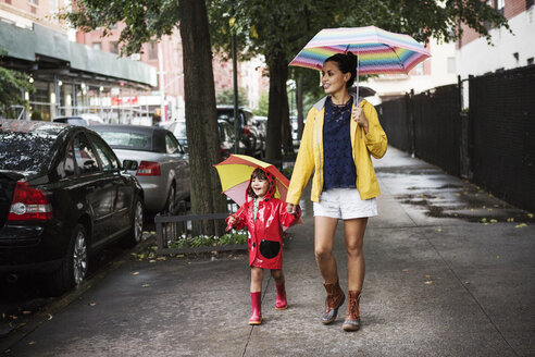 Happy mother and daughter holding umbrellas while walking on sidewalk - CAVF22408