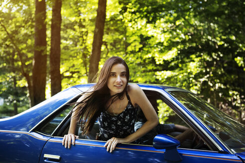 Portrait of woman leaning out of pick-up truck window in forest - CAVF22456