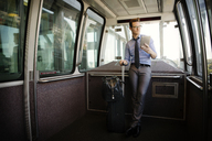 Businessman holding tablet computer and luggage while standing in train - CAVF22522