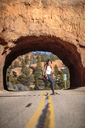Hiker skateboarding on road against rocky tunnel at Bryce Canyon National Park - CAVF22576