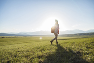 Full length of female hiker walking on grassy field against sky - CAVF22606