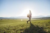 Full length of female hiker walking on grassy field against sky - CAVF22606