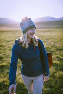 Happy female hiker looking away while walking on grassy field - CAVF22609