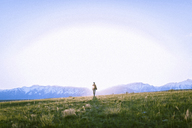 Female hiker standing on grassy field against mountains - CAVF22612