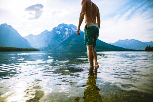 Low section of man standing in lake against mountains and sky - CAVF22615