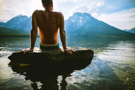 Shirtless man relaxing on rock in lake against mountains - CAVF22618