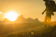Low section of hiker with backpack walking on grassy field against mountains during sunset - CAVF22630