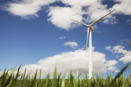 Low angle view of wind turbine on grassy field against sky - CAVF22663