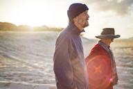 Happy senior couple walking at beach on sunny day - CAVF22771