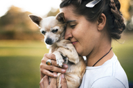 Side view of smiling woman holding Chihuahua on field - CAVF22822