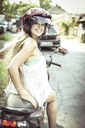 Portrait of smiling woman sitting on motor scooter - CAVF22900