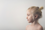 Side view of cute shirtless girl standing against wall at home - CAVF22945
