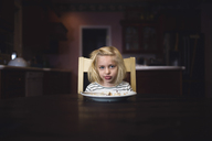 Portrait of cute girl making face while sitting at table - CAVF22951