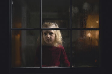 Portrait of thoughtful girl seen through wet glass window at night - CAVF22954