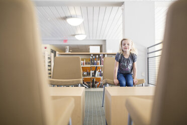 Portrait of smiling girl sitting on chair at library - CAVF22957