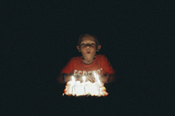 Cute boy blowing birthday candles in darkroom - CAVF22960