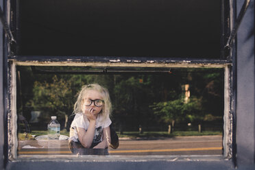 Thoughtful girl wearing eyeglasses leaning on table seen through glass - CAVF22969