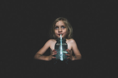 Shirtless girl drinking juice while sitting in darkroom at home - CAVF22975
