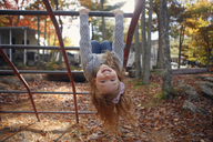 Portrait of happy girl playing on jungle gym in playground during autumn - CAVF23035