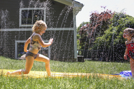 Happy siblings playing with water on grassy field at backyard - CAVF23089