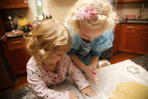 High angle view of happy sisters making cookies in kitchen at home - CAVF23110