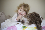 Happy girl relaxing with dog on bed at home - CAVF23119