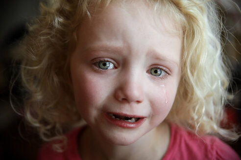 Close-up portrait of girl crying at home - CAVF23140
