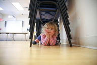 Thoughtful girl lying under stacked chairs on floor at home - CAVF23143