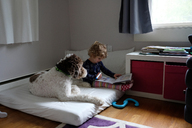 Girl studying while sitting by dog on mattress at home - CAVF23152