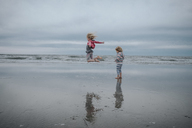 Carefree girl jumping while sister standing at beach against sky - CAVF23176
