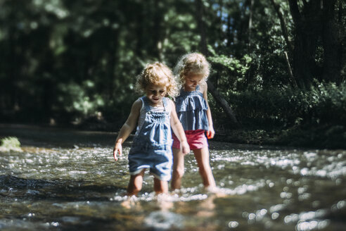 Sisters wading in lake during sunny day - CAVF23188