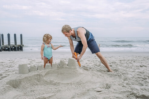 Father making sand castle by daughter at Cape May Beach against sky - CAVF23203