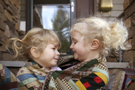 Happy sisters wrapped in blanket sitting in porch - CAVF23215