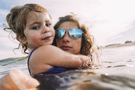 Portrait of mother and daughter swimming in sea - CAVF23236