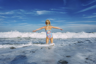 Rear view of girl with arms outstretched standing in sea against cloudy sky - CAVF23239