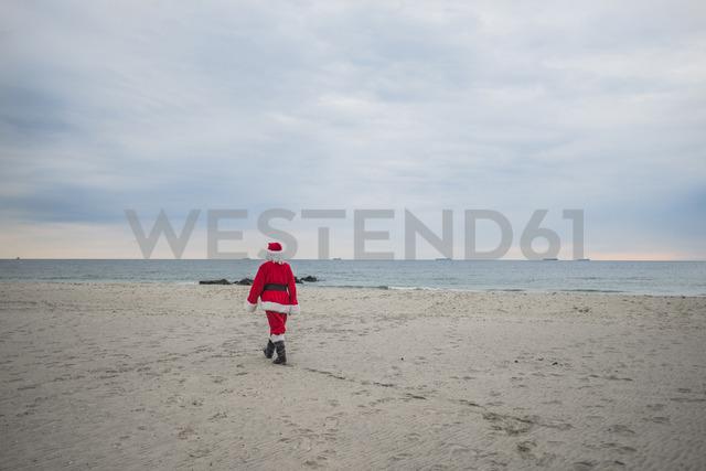 Rear view of senior man in Santa costume walking at beach - CAVF23254