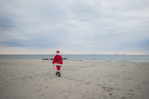 Rear view of senior man in Santa costume walking at beach - CAVF23254