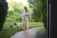 Woman walking with dog on pathway in yard - CAVF23269