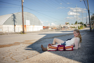 Thoughtful woman lying on sidewalk in front of factory - CAVF23296