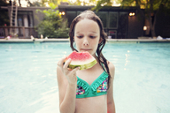 Girl eating watermelon slice while standing against swimming pool - CAVF23305