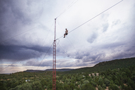 Low angle view of man sitting on tight rope against cloudy sky - CAVF23317