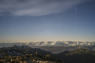 Distant view of hiker standing amidst mountains against star field sky - CAVF23476