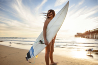 Woman holding surfboard and standing at beach on sunny day - CAVF23512