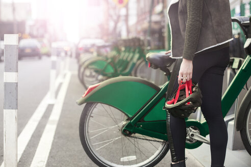 Midsection of woman standing by bike share on sidewalk - CAVF23533