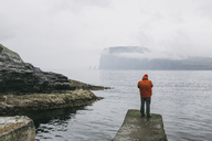 Rear view of hiker in hooded jacket standing on pier against sea during foggy weather - CAVF23554