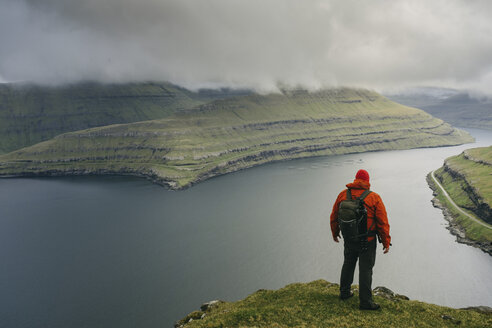 Hiker with backpack looking at view while standing on cliff against stormy clouds - CAVF23584