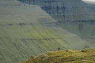 Distant view of hiker standing on cliff by mountains - CAVF23611