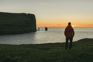 Hiker looking at view while standing by sea during sunset - CAVF23635