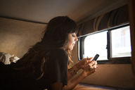 Woman using smart phone while relaxing on bed in camper van - CAVF23680